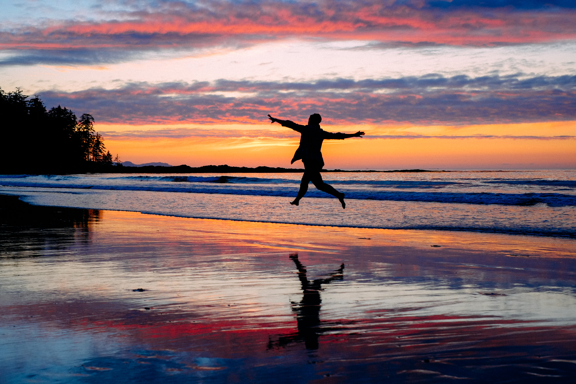 A woman jumps into the air at sunset on the beach.