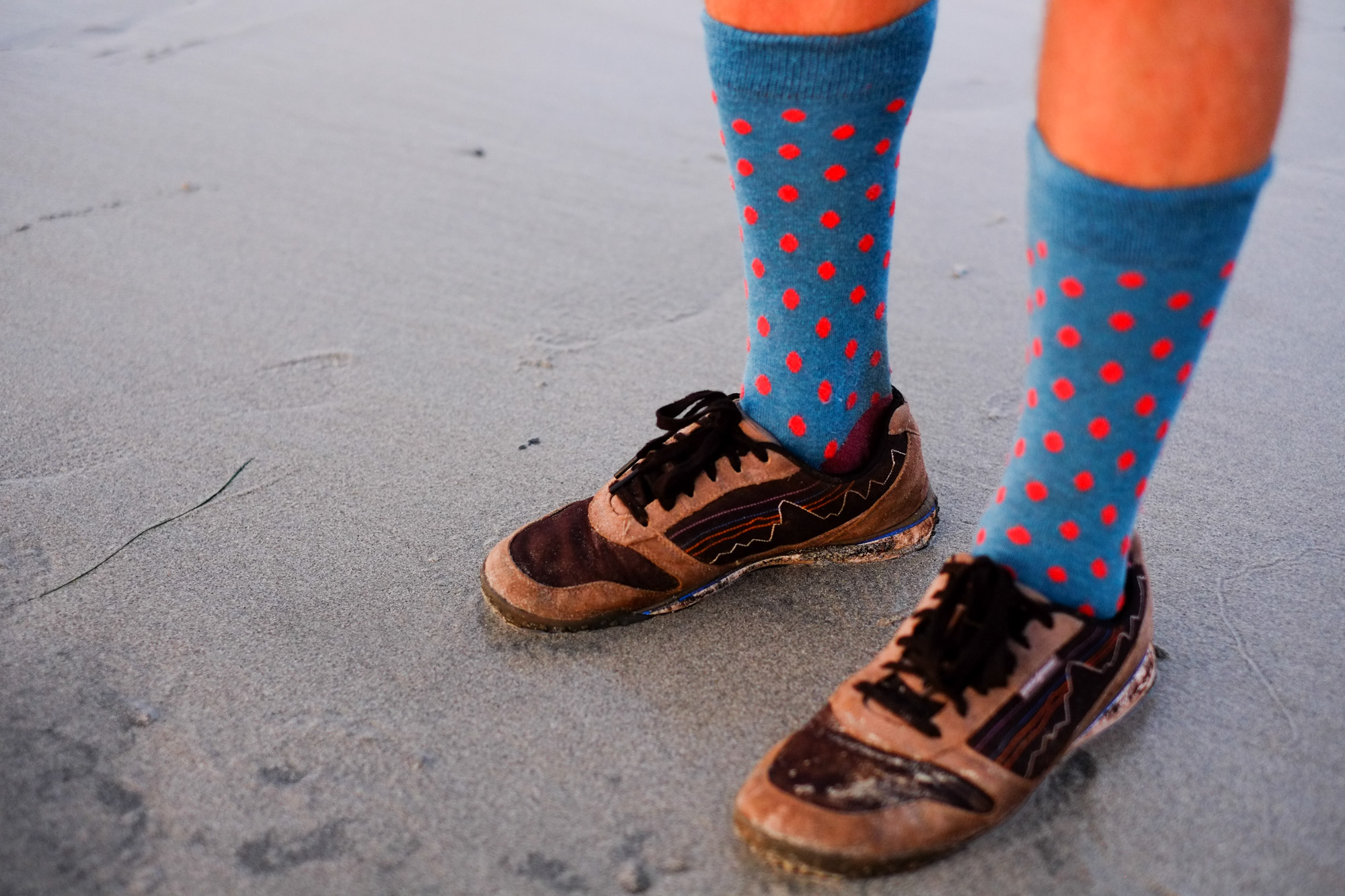 A man with colorful socks and Patagonia shoes.